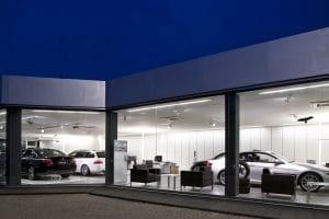 Außenansicht Autohaus im Dunkeln mit Blick nach Innen durch Fensterwand