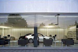 Außenansicht Autohaus mit Blick nach Innen durch Fensterwand