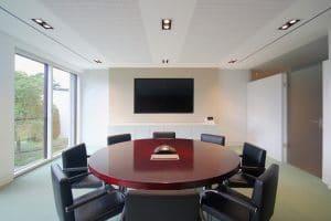 Büroraum runder Tisch, Stühle und Wandfernseher