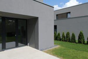 Außenansicht graues Haus mit Terrasse und Wiese