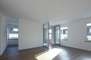Heller Raum mit dunklem Boden und vielen Fenstern
