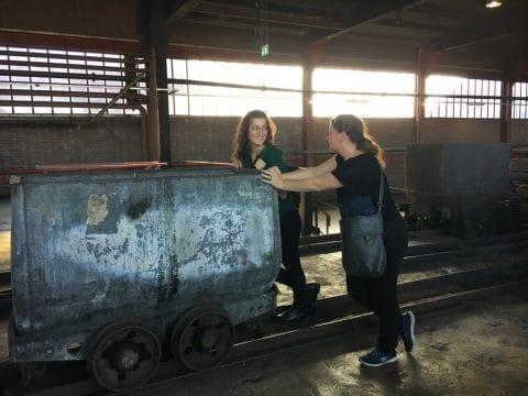 Mitarbeiter schieben Waggon auf Schienen