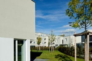 Außenansicht hellgraue Wohnungen und Wiese mit Bäumen