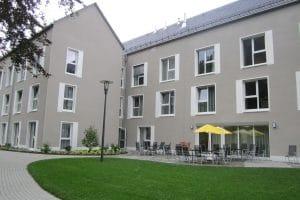 Graues Haus mit Terrasse, mehrere Tische und Stühle