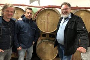 Geschäftsführer und Mitarbeiter vor Weinfässern